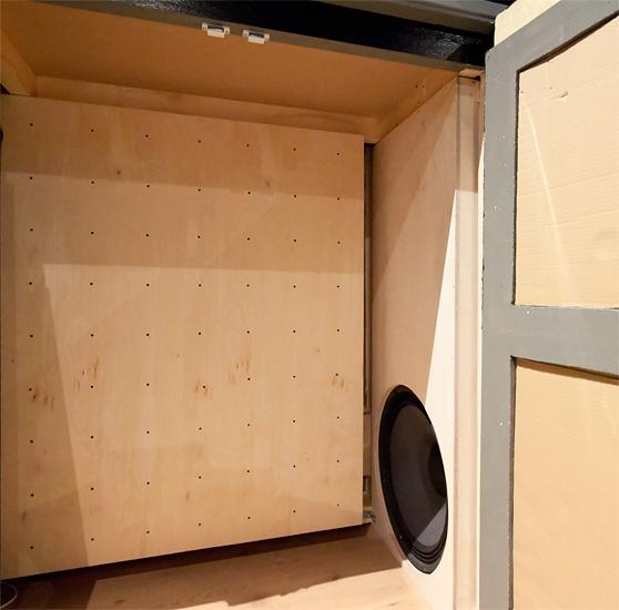 Takaseinän kaapin pohjalla piilottaa bassovaimennin ja toinen subwoofereista. 20 senttiä syvässä vaimentimessa on 6,5-millinen vanerinen etulevy, jossa on 6 mm reikiä 125 mm päässä toisistaan. Kotelon syvyydestä taaempi puolikas on täytetty lämpöeristysvillalla.